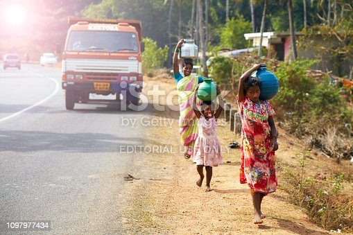India, Hampi - March 18, 2017: rural Indian women carry water on their heads in traditional pots, EDITORIAL.