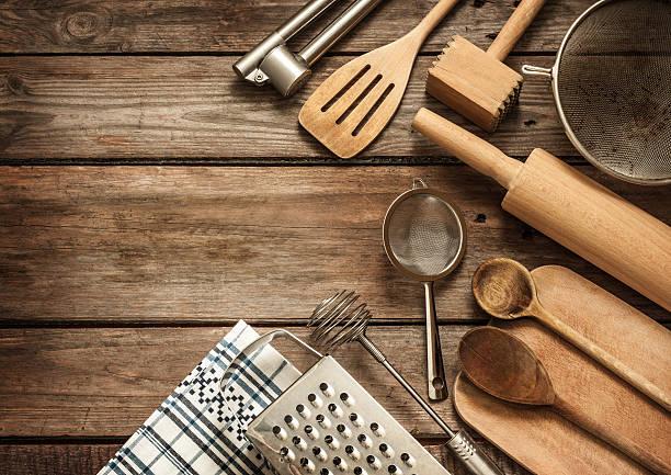 rural kitchen utensils on vintage planked wood table - keukengereedschap stockfoto's en -beelden