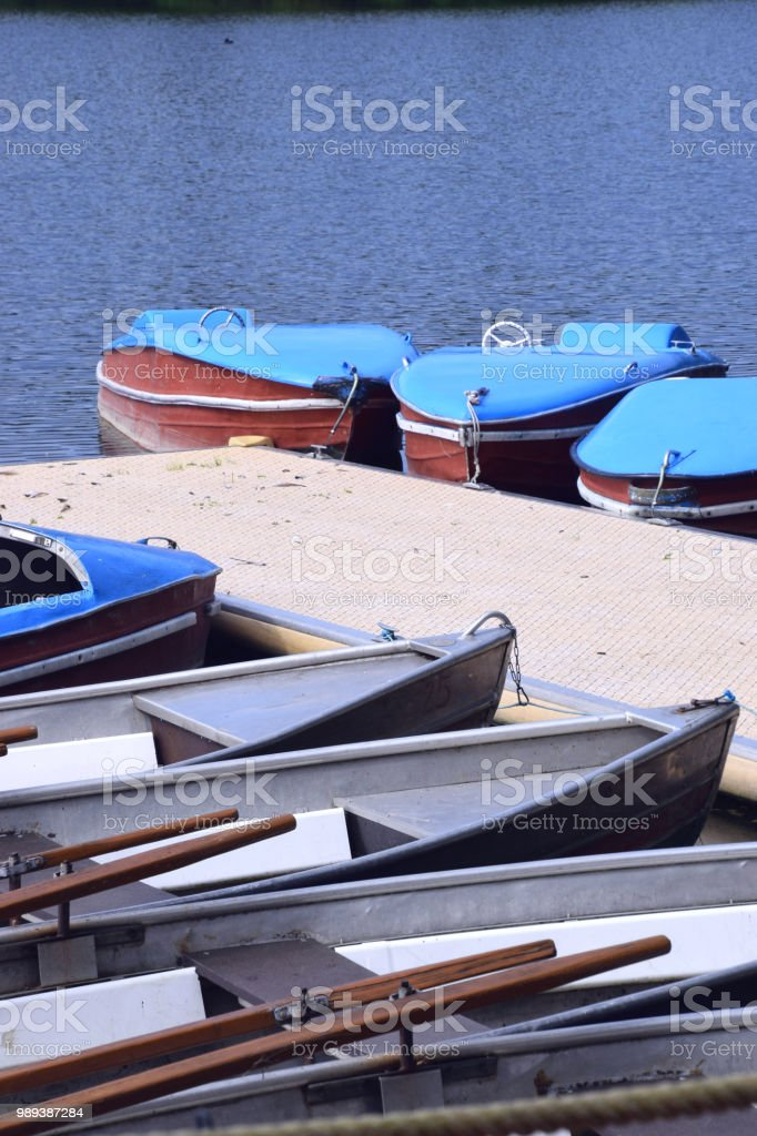 old and nostalgic pedal boats and row boats on a pier