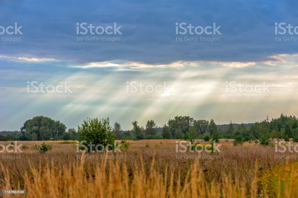Rural landscape and sun rays through clouds stock photo