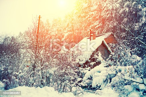 1061644120 istock photo Rural landscape. Forest covered with snow. Snowy winter. Old hut in the forest. Christmas background. Pine trees in snow 1044980082