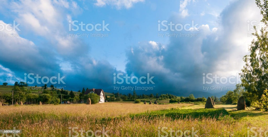 Rural landscape with haystacks in a summer sunny day. Rural mountain landscape with storm clouds. stock photo