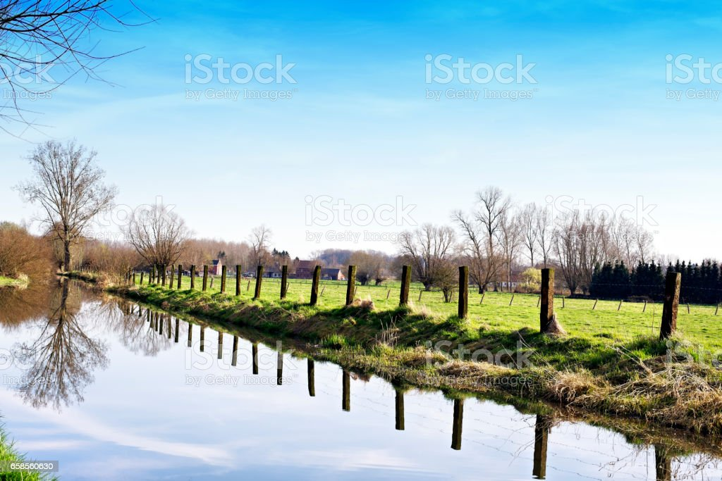 Rural landscape with pasture and a row of poles  reflected in the Zwalm River in East Flanders,Belgium stock photo
