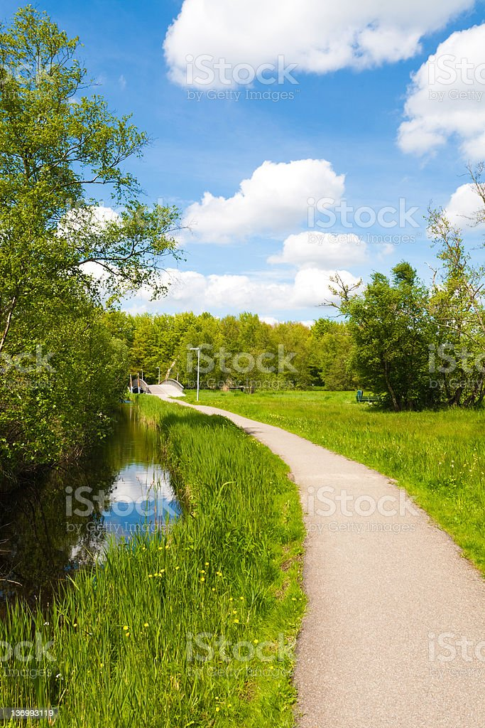 rural landscape with path, bridge, and fluffy clouds royalty-free stock photo