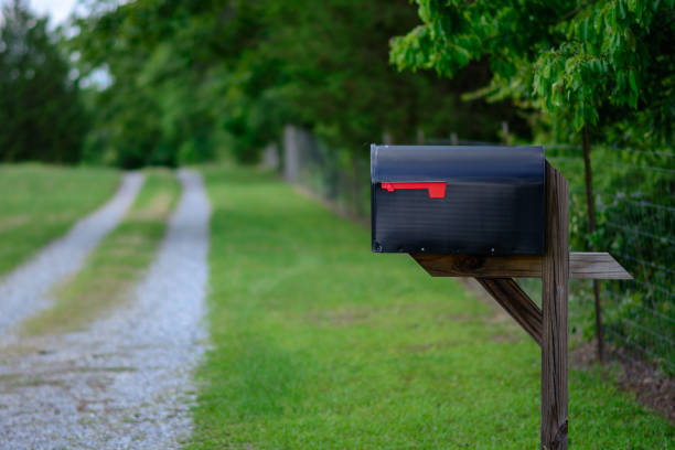 Rural mailbox gravel road A large mailbox with the flag down along a gravel road. mailbox stock pictures, royalty-free photos & images