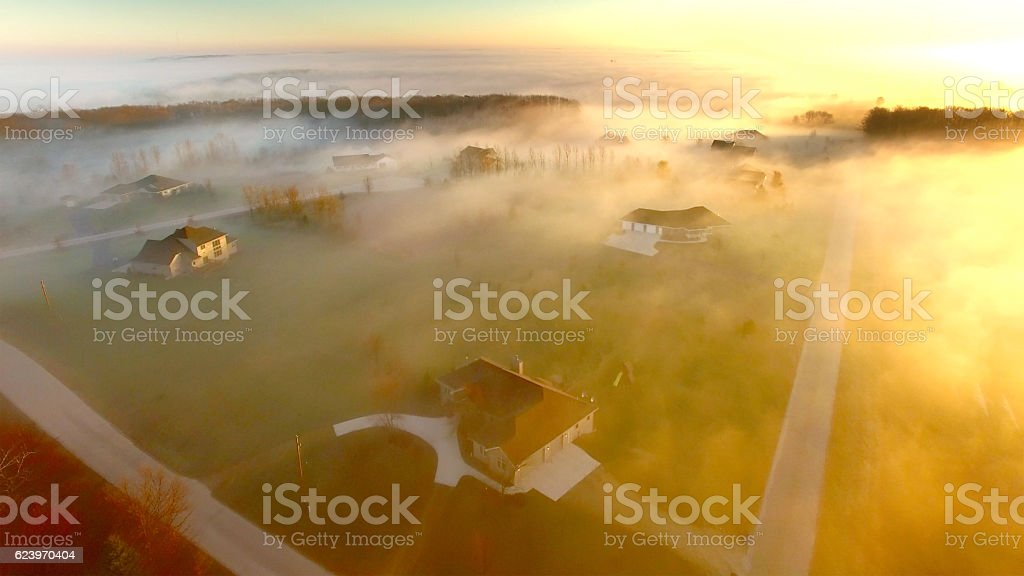 rural neighborhood under ethereal fog at dawn stock photo