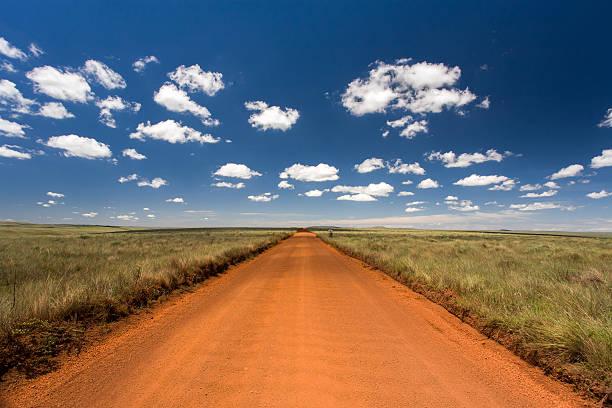 Rural orange dirt road with blue sky and far horizon stock photo