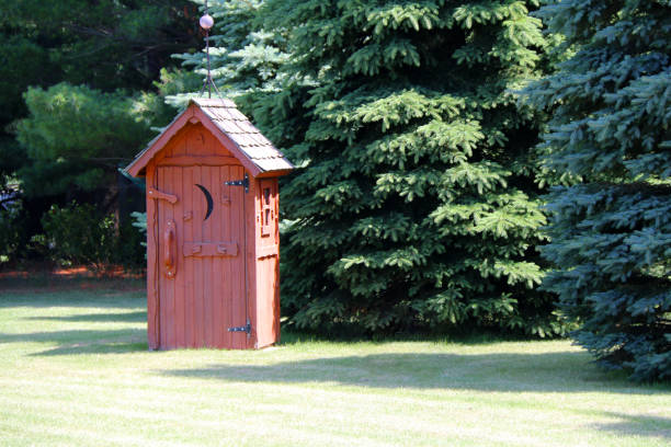 rural red outhouse privy toilet building forest glade stock photo