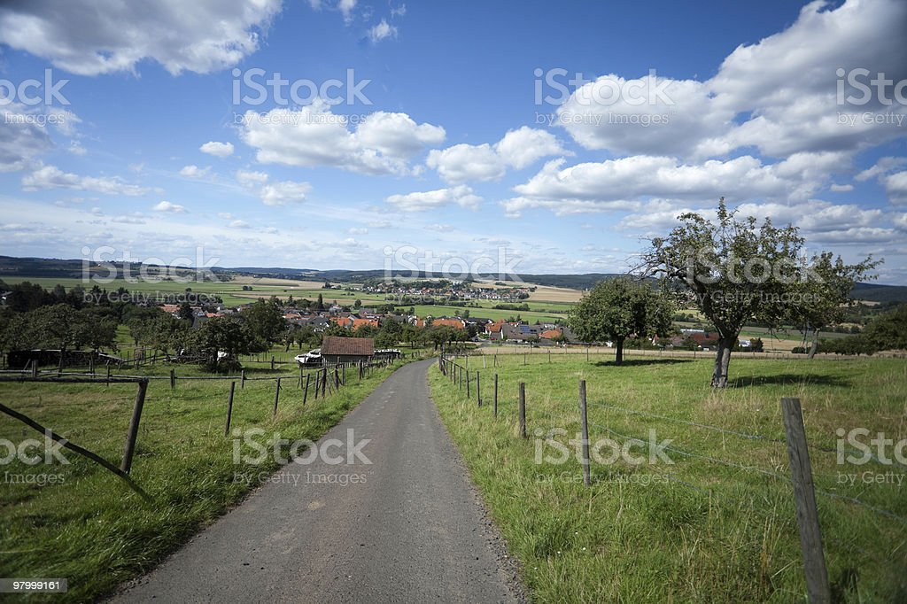 rural road country town idyllic scene green grass white clouds royalty-free stock photo