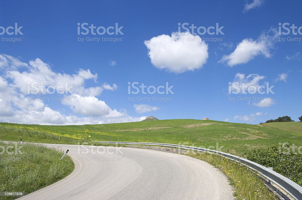 rural road crosses green hill, blue sky and white clouds royalty-free stock photo