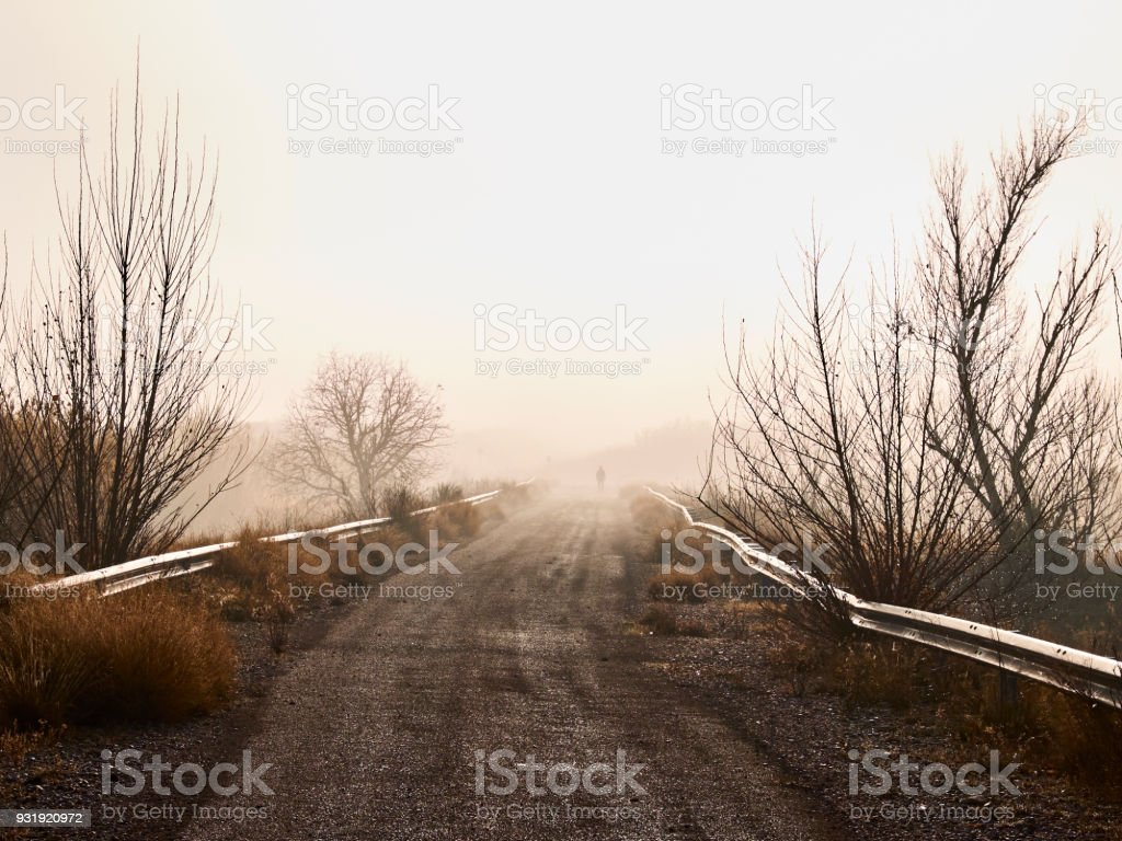 Rural road entering the fog, with one person in the background stock photo