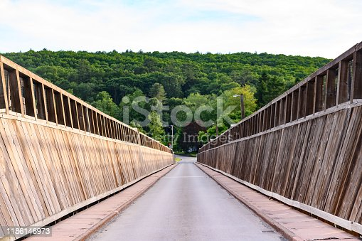This is a photograph of the scenic road crossing from New York to Pennsylvania states over Delaware River via the historic Roebling Bridge (Roebling's Delaware Aqueduct) in spring.