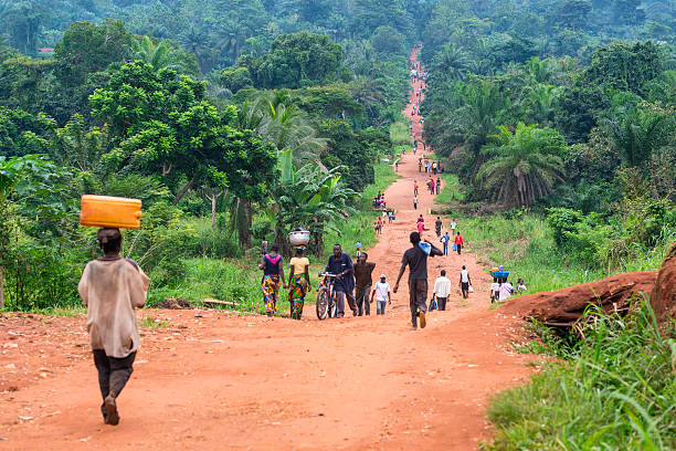 rural road with a lot of pedestrians, dr congo - democratic republic of the congo stock photos and pictures