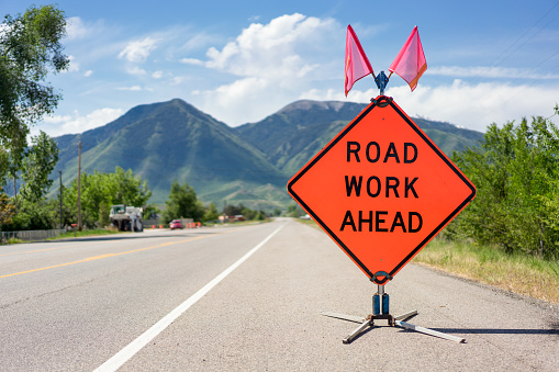 A bright orange 'Road Work Ahead' warning sign on a country highway in Utah, USA.