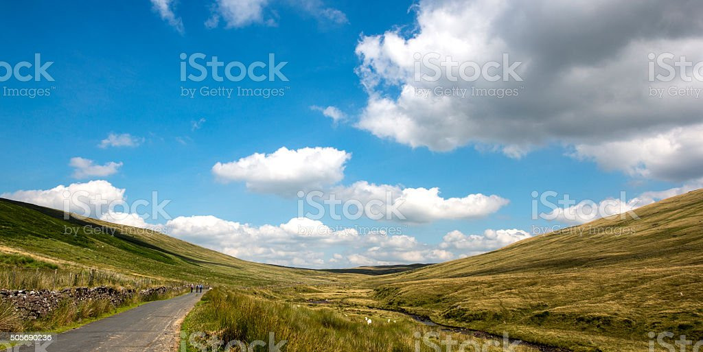 Rural scene with blue cloudy sky  with walkers on road stock photo