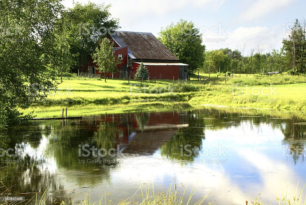 Rural Scene with red barn and pond stock photo