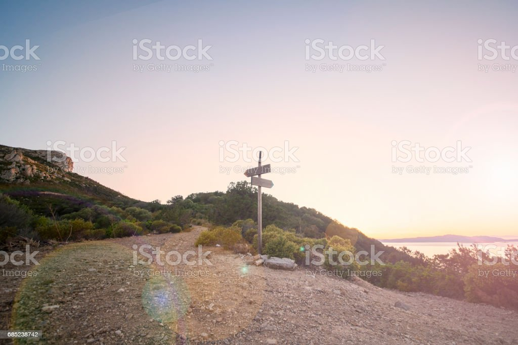 Rural scenic landscape with crossroad on hill in forest at sunset. Two different directions. Concept of choose the correct way. Right and left path. Junction, fork, split road. stock photo