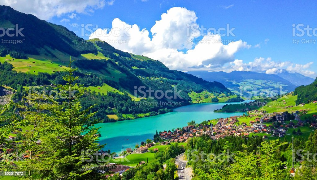 Rural Swiss Scenery from Train Ride Window View, Picturesque Picture as a Painting of Lungern Village and Lake in a beautiful summer day, Lungern, Switzerland, Europe. stock photo