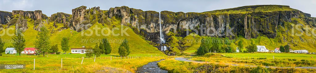 Rural village below picturesque waterfall and cliffs panorama Iceland stock photo