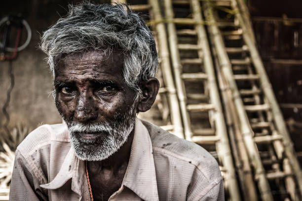 Rural village dark skin Indian old man Portrait of Indian elder man with traditional bindi as a third eye, white beard and bamboo ladders on the background in Mysore, Karnataka, India. Concerned expression one senior man only stock pictures, royalty-free photos & images