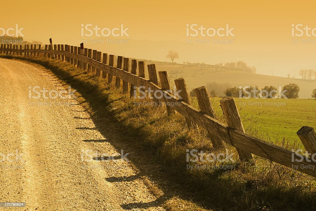 Rural village road with fields and sky in background royalty-free stock photo