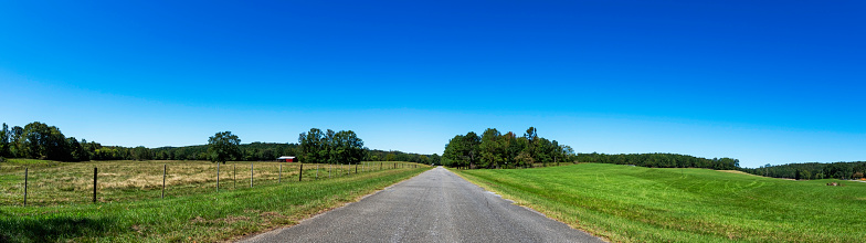 Panoramic web banner of an empty country road with farmland on either side and negative space above.
