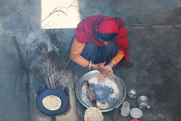 Rural women making chapatti on Wood burning stove (Chulha) stock photo