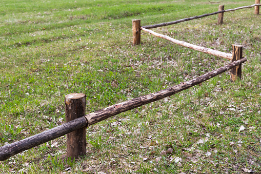 Rural wooden fence made of logs, land areas border markings