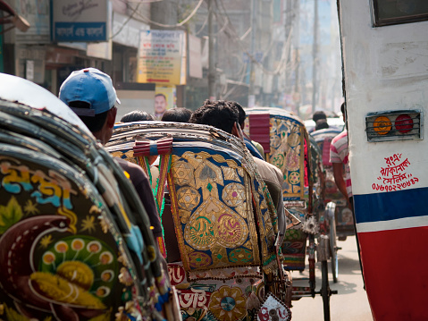 Dhaka, Bangladesh - January 23, 2012: Street full of colorful and brightly decorated rickshaws on the left side and a bus on the right, photographed from behind during rush hour in Dhaka city in Bangladesh.