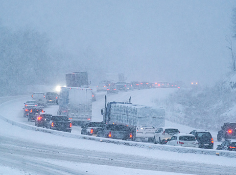 Rush hour traffic is delayed during heavy snowfall.