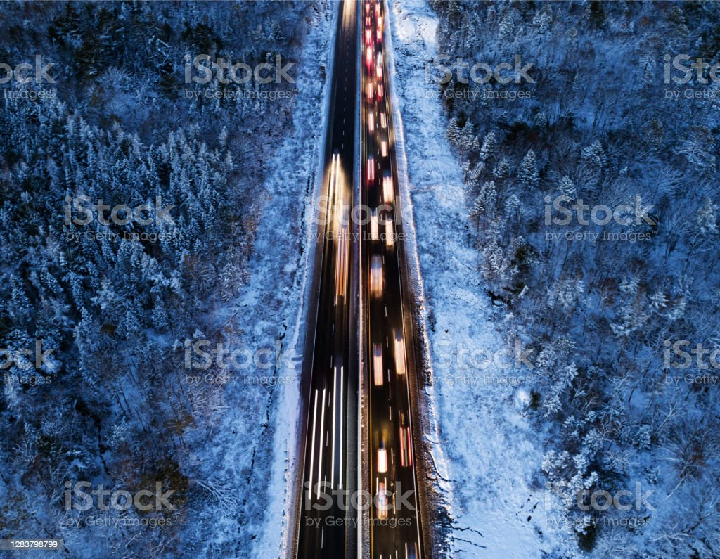 Rush Hour Traffic in Winter Aerial drone view of highway traffic during the fist snowfall of the season. Aerial View Stock Photo