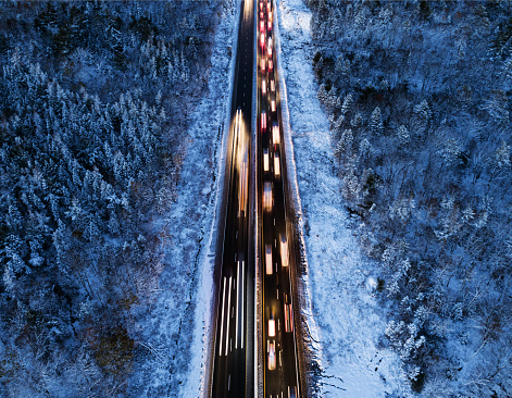 Aerial drone view of highway traffic during the fist snowfall of the season.