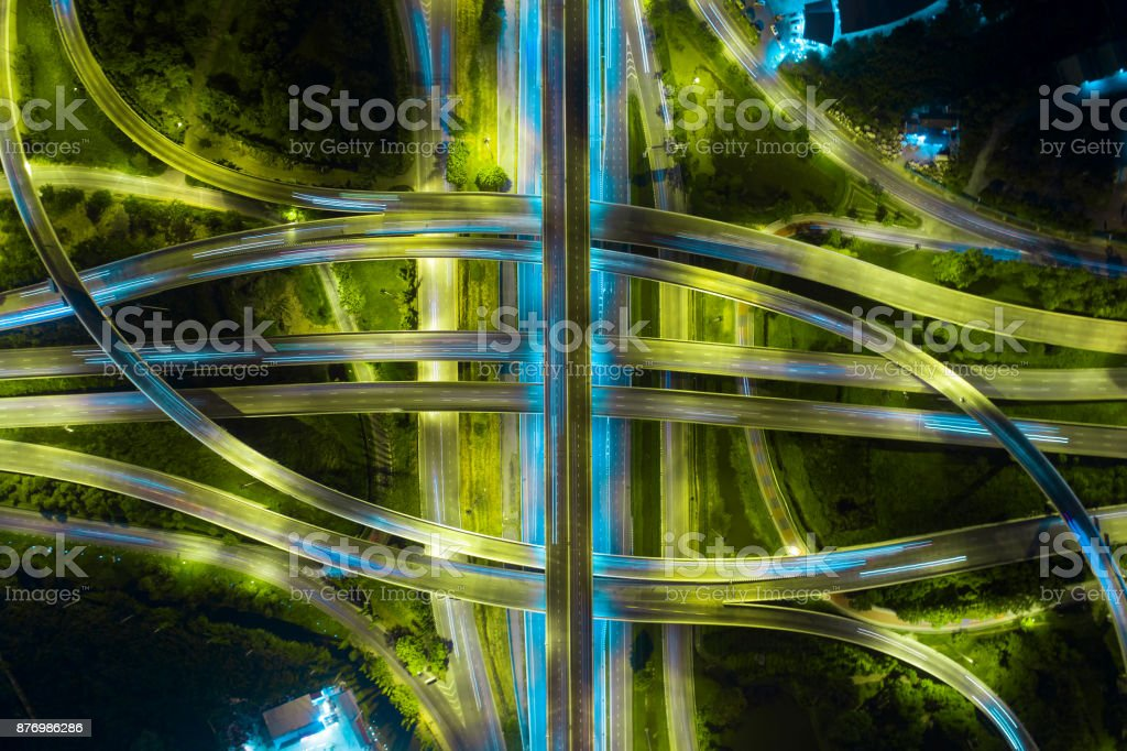 Rush hour traffic on a city roads. Rush hour traffic on a city roads. Modern metropolis with intersection of the traffic trails on a highway. Traffic jams of roadside, transportation motion in a big city. Above Stock Photo