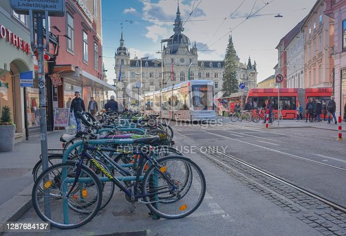 Graz, Austria - November 18, 2019: Rush hour with lots of people, trams, cyclist and cars in main square Hauptplatz , Town Hall building in the background, in Graz, Styria region, Austria.