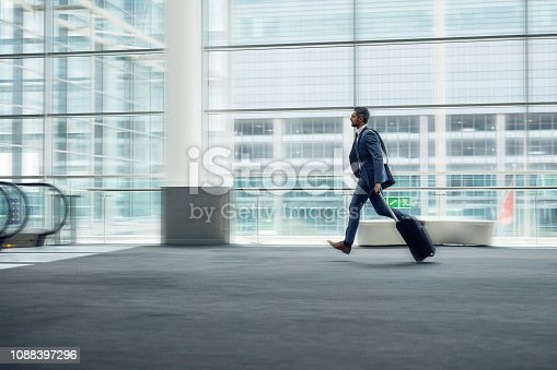 Shot of a mature businessman rushing through an airport