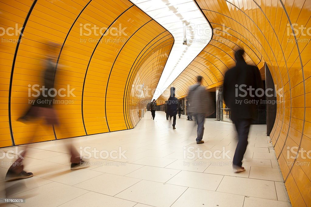 rushing commuters against modern orange background stock photo