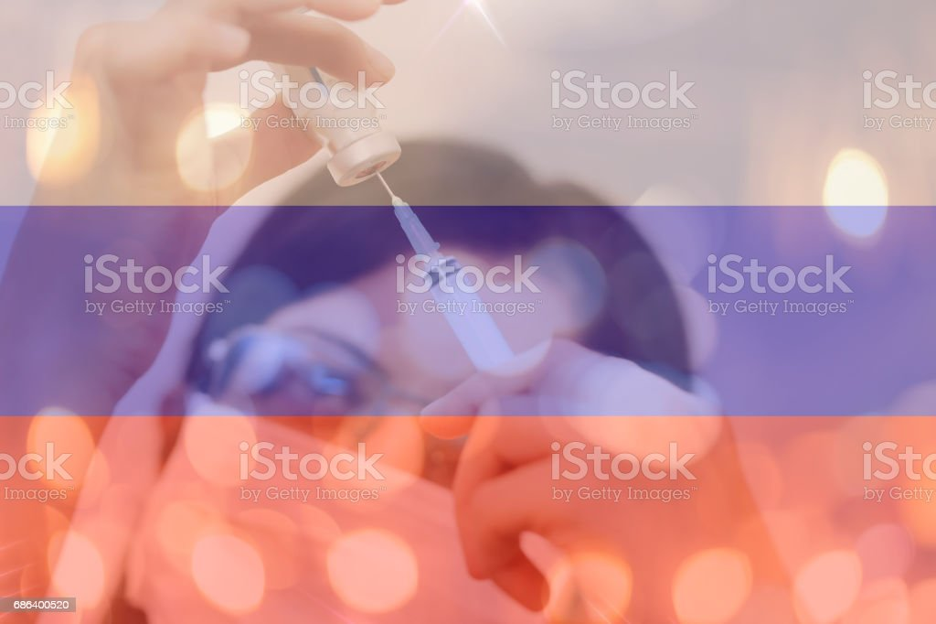 Russia and cancer vaccine, young chemical female researcher holding syringe and ampoule with fluid in laboratory. Russia flag with female doctor stock photo