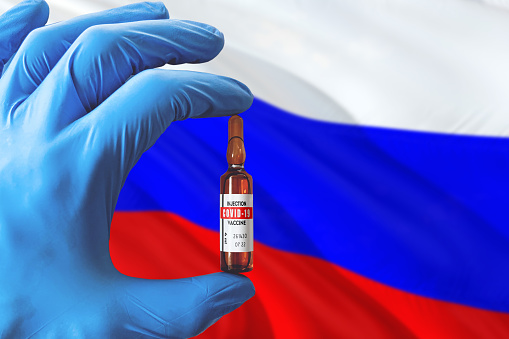Russia flag with Coronavirus Covid-19 concept. Doctor with blue protection medical gloves holding a vaccine bottle. Epidemic Virus, Cov-19, Corona virus outbreaking.