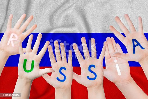 Russia inscription on the children's hands against the background of a waving flag of the Russian Federation.