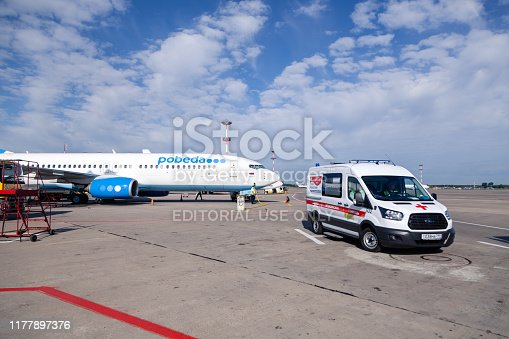istock Russia Moscow 2019-06-17 Ford ambulance car on the background of the airport runway, large wide body passenger aircraft Boeing 737 of Pobeda Airlines 1177897376