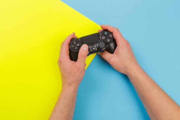 rusland, oktober 24 2019: mannelijke handen vasthouden van een ps4 controller, sony playstation 4 game console. - playstation stockfoto's en -beelden