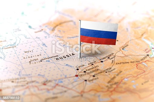 The flag of Russia pinned on the map. Horizontal orientation. Macro photography.