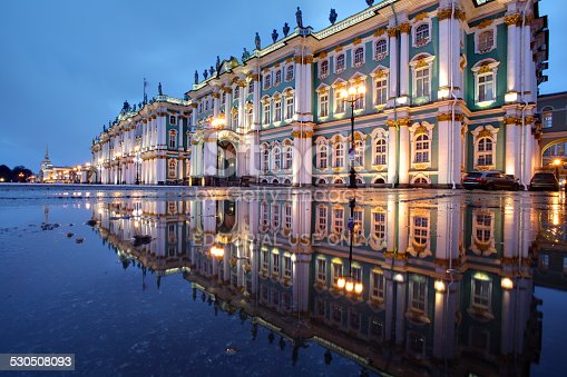 St. Petersburg, Russia - December 18, 2014: The building of the Winter Palace, which houses the Hermitage Museum at night illumination, reflected in the water paving puddle.