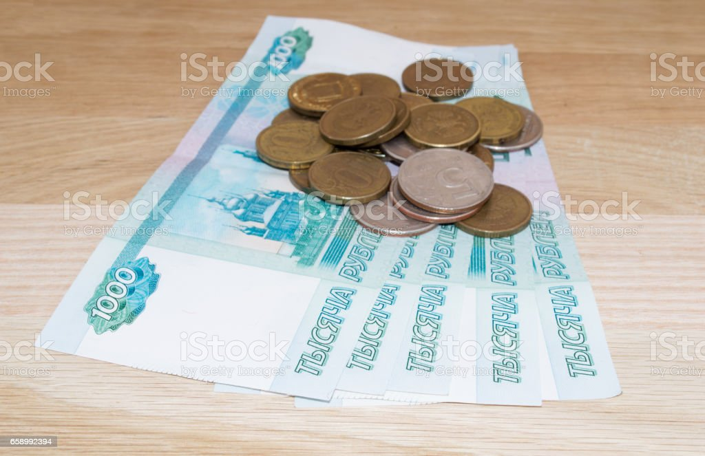 Russian 1000 rubles with coins on wooden background royalty-free stock photo