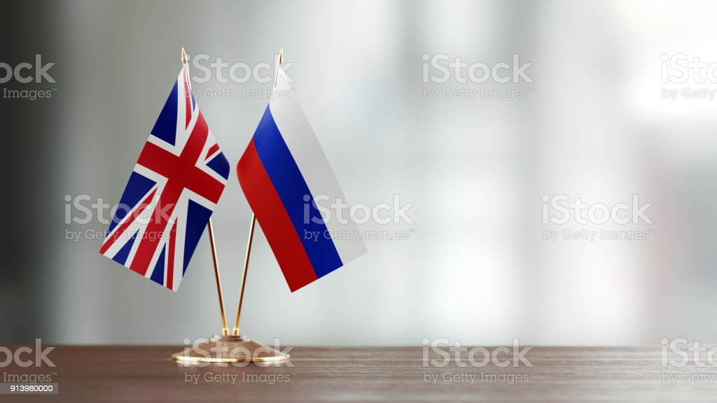 Russian And British Flag Pair On A Desk Over Defocused Background stock photo