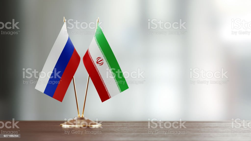 Russian And Iranian Flag Pair On A Desk Over Defocused Background stock photo