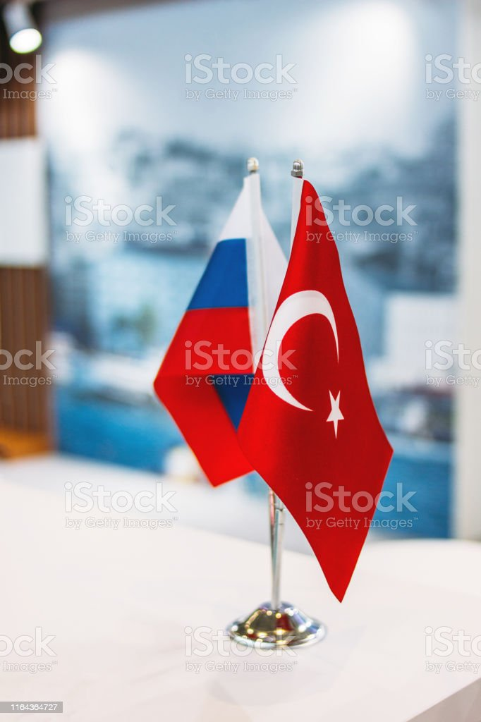 Russian and Turkish flags on metal stand on the business conference...