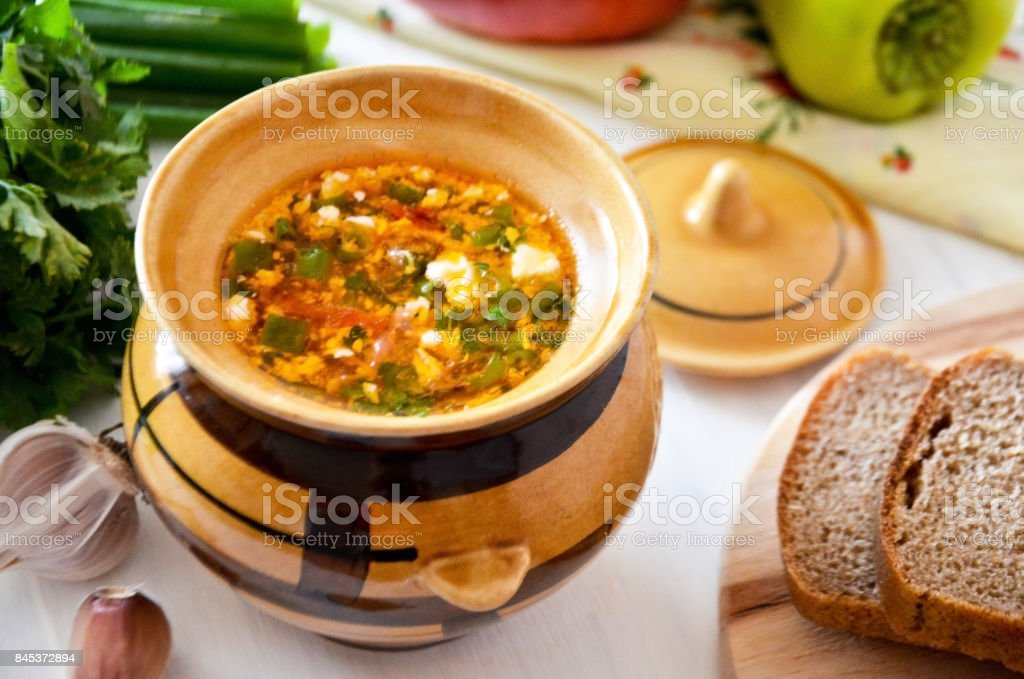 Russian borsch in clay pot with herbs and sour cream stock photo