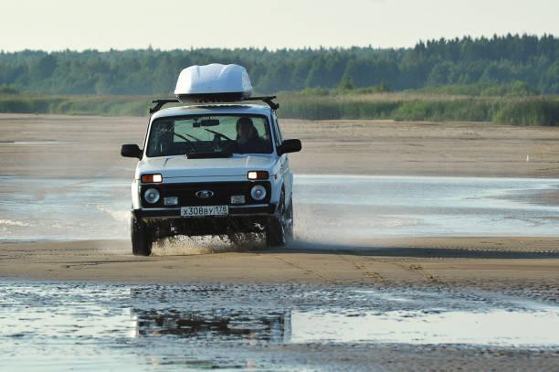 russisches auto niva fährt auf einer küstenstraße mit spritzern unter den rädern - lada niva stock-fotos und bilder