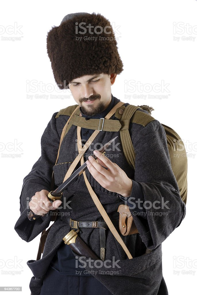 Russian Cossack inspecting a poniard. The living history. royalty-free stock photo